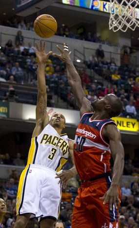 Indiana Pacers guard George Hill (3) puts up a shot over the defense of Washington Wizards center Emeka Okafor (50) during the second half of an NBA basketball game in Indianapolis, Saturday, Nov. 10, 2012. The Pacers defeated the Wizards 89-85. (AP Photo/Doug McSchooler)