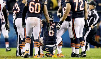 Chicago quarterback Jay Cutler (above) is helped to his feet by teammates after being leveled by Houston linebacker Tim Dobbins during the first half Sunday night. (Associated Press)