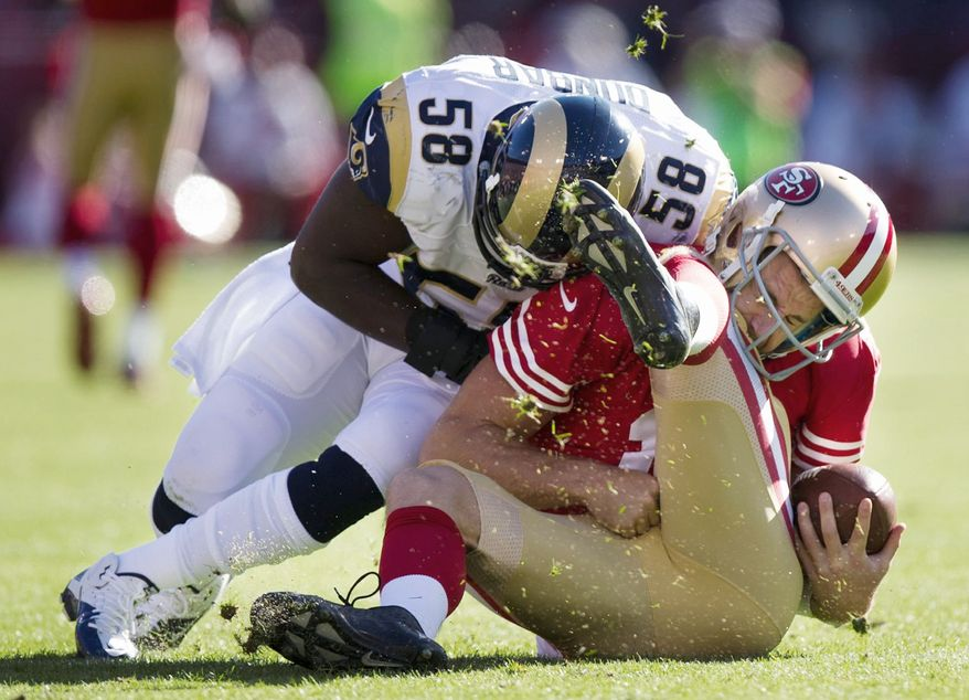 San Francisco quarterback Alex Smith folds under the pressure of a hit by St. Louis linebacker Jo-Lonn Dunbar on Nov. 11, 2012. Smith later left the game with a concussion.