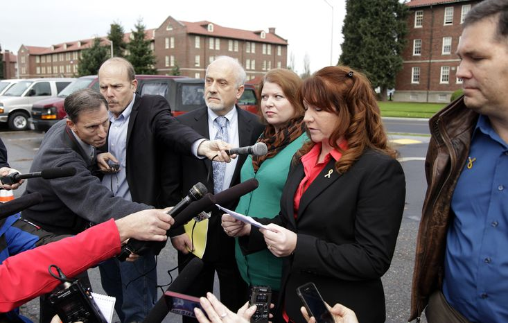 Kari Bales (third from right) stands next to attorney Lance Rosen (third from left) as she listens to her sister, Stephanie Tandberg (second from right), read a statement to reporters on Nov. 13, 2012, outside the building housing a military courtroom on Joint Base Lewis McChord in Washington state, where a preliminary hearing ended for Kari's husband, U.S. Army Staff Sgt. Robert Bales. Bales is accused of 16 counts of premeditated murder and six counts of attempted murder for a pre-dawn attack on two villages in Kandahar Province in Afghanistan in March of 2012. At right is Stephanie's husband, Eric Tandberg. (Associated Press)