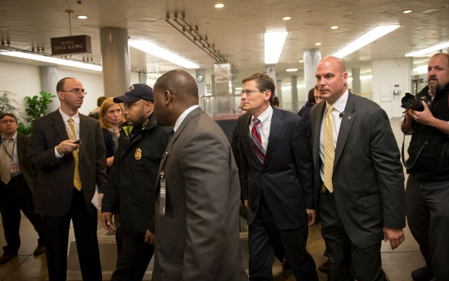 Acting CIA Director Michael Morell (in red tie) is escorted past a gauntlet of reporters as he arrives at the U.S. Capitol in Washington, D.C., Tuesday, Nov. 13, 2012, for a closed Senate Foreign Relations briefing on the attacks in Benghazi, Libya. (Rod Lamkey Jr./The Washington Times)