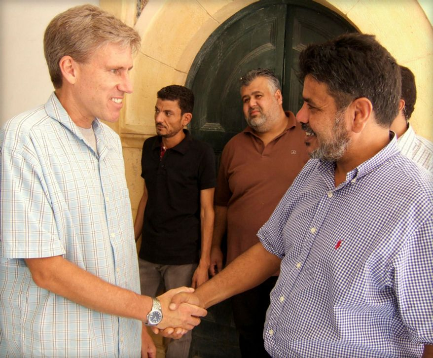 **FILE** In this photo posted on the U.S. Embassy Tripoli Facebook page on Aug. 27, 2012, Christopher Stevens (left), U.S. Ambassador to Libya, shakes hands with a Libyan man in Tripoli, Libya. (Associated Press/U. S. Embassy Tripoli)