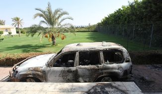 A burnt car sits in front of the U.S. Consulate in Benghazi, Libya, after an attack that killed four Americans, including Ambassador Chris Stevens, on the night of Sept. 13, 2012. (Associated Press)