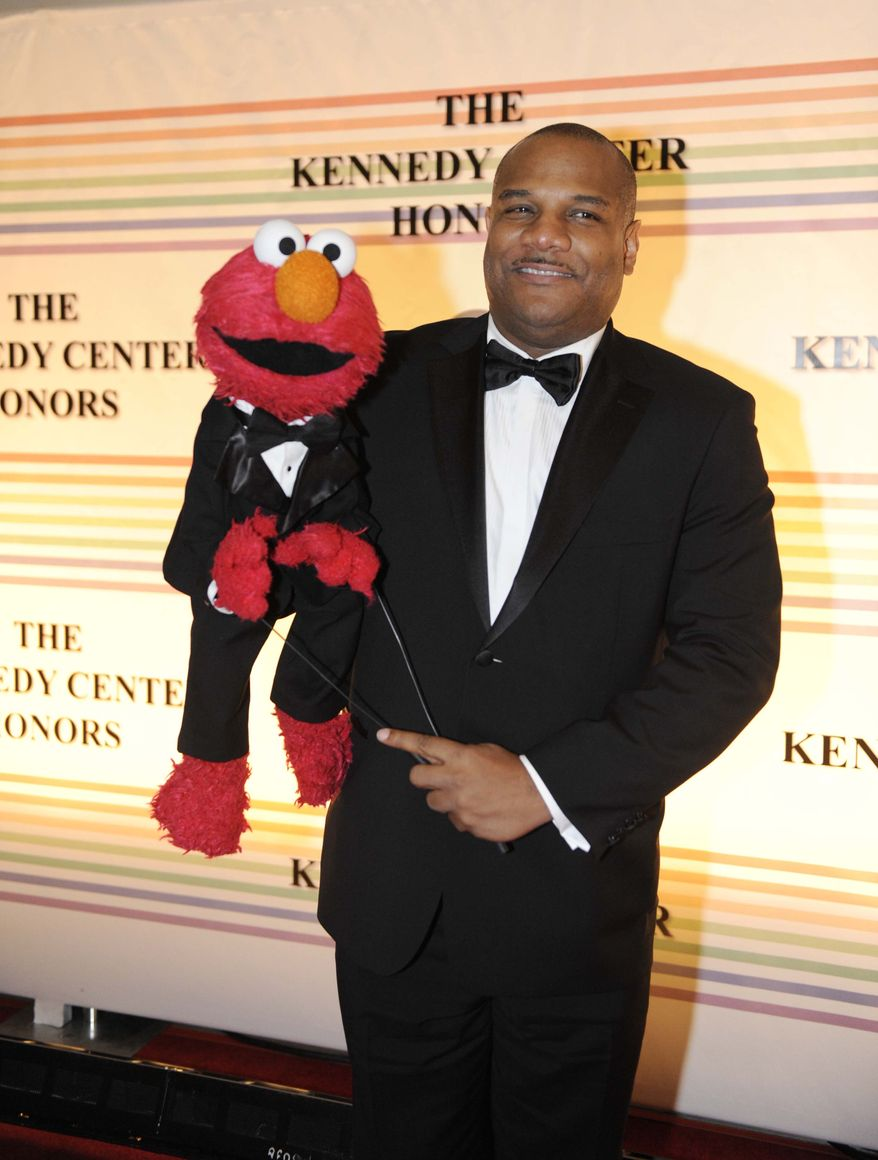 """FILE - In this Dec. 4, 2011 file photo, Elmo puppeteer Kevin Clash arrives with the """"Sesame Street"""" muppet at the Kennedy Center for the Performing Arts for the Kennedy Center Honors gala performance in Washington. The man who accused Clash of having sex with him when he was a teen now says it isn't so. The man said in a statement released on Tuesday, Nov. 13, 2012 that his sexual relationship with Clash was adult and consensual. (AP Photo/Kevin Wolf, File)"""