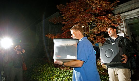 FBI agents carry boxes and a computer from the home of Paula Broadwell, the woman whose affair with retired Gen. David Petraeus led to his resignation as CIA director, in the Dilworth neighborhood of Charlotte, N.C., on Nov. 13, 2012. (Associated Press)