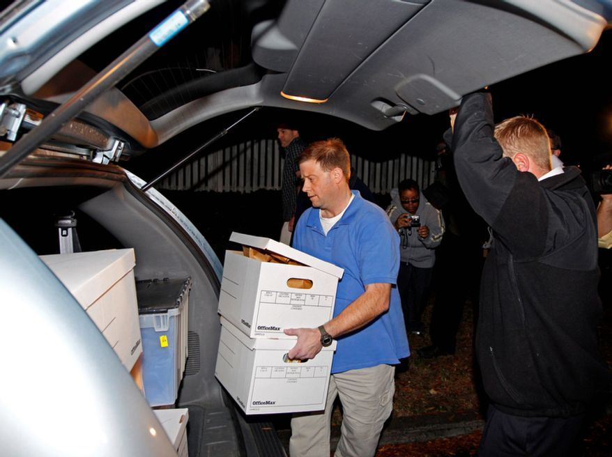 FBI agents carry boxes from the home of Paula Broadwell, the woman whose affair with retired Gen. David Petraeus led to his resignation as CIA director, in the Dilworth neighborhood of Charlotte, N.C., on Nov. 13, 2012. (Associated Press)