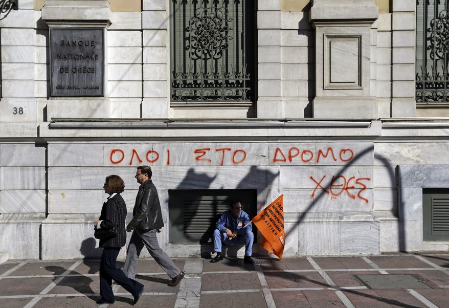 "A municipal worker participating in a anti-austerity rally sits Nov. 9, 2012, in central Athens in front of the National Bank of Greece building, underneath graffiti reading in Greek ""All to the streets yesterday."" (Associated Press)"