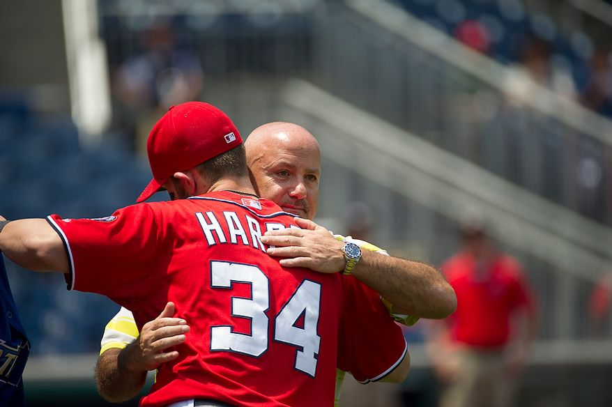 Nationals General Manager Executive Vice President of Baseball Operations Mike Rizzo gives a hug to Bryce Harper (34) prior to the game as the Washington Nationals host the Colorado Rockies at Nationals Park in Washington, D.C., Sunday, July 8, 2012. (Rod Lamkey Jr./The Washington Times)
