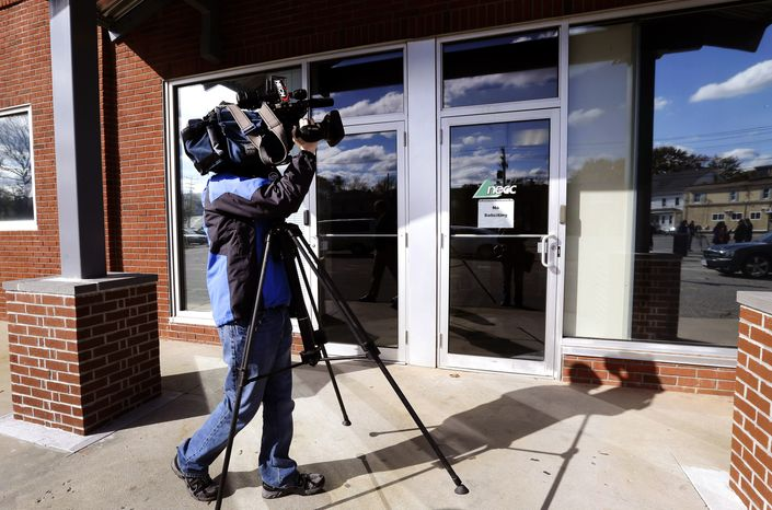 In this Thursday, Nov. 1, 2012, photo, a TV news photographer shoots the facade of the New England Compounding Center, which has since been linked to a recent deadly meningitis outbreak, in Framingham, Mass. According to a congressional investigation released Tuesday, Nov. 13, 2012, federal health inspectors wanted to shut down the New England Compounding Center, until it cleaned up its operations in 2002. Nearly 440 people have been sickened by contaminated steroid shots distributed by New England Compounding Center, and more than 32 deaths have been reported since the outbreak began in September, according to the Centers for Disease Control and Prevention. (AP Photo/Elise Amendola)