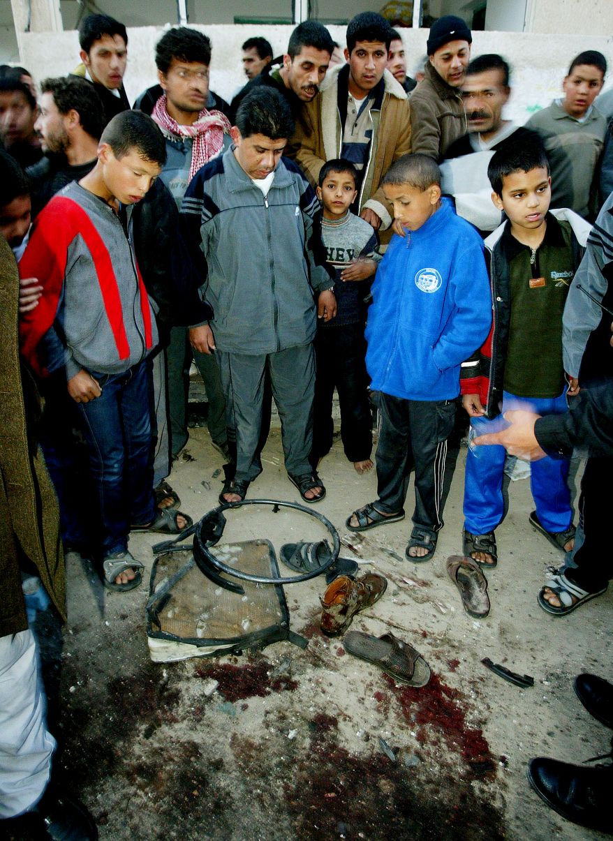 **FILE** Palestinians gather March 22, 2004, around a pool of blood and the remains of the wheelchair of Hamas spiritual leader Sheikh Ahmed Yassin, following an Israeli air strike that killed him, near his house in Gaza City. (Associated Press)