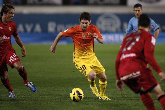 FC Barcelona's Lionel Messi from Argentina drives the ball next to RCD Mallorca's Joaquín Navarro Ximo, right, and Tomás Pina, left, during a Spanish La Liga soccer match in Mallorca, Spain, Sunday, Nov. 11, 2012. (AP Photo/Tolo Ramon)