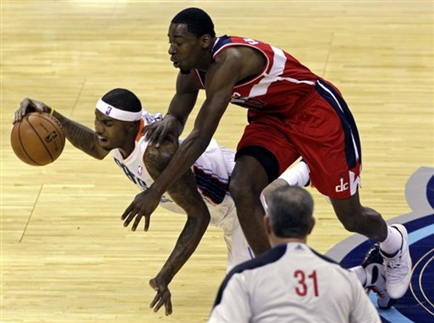 Charlotte Bobcats' Tyrus Thomas, left, is fouled by Washington Wizards' Jordan Crawford during the first half of an NBA game in Charlotte, N.C., Tuesday, Nov. 13, 2012. (AP Photo/Chuck Burton)