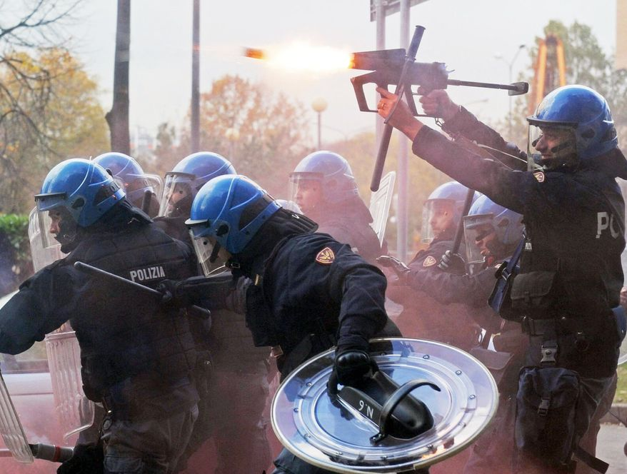 An officer fires tear gas as police face demonstrators during a protest against government austerity measures in Turin, Italy, on Wednesday. Protesters clashed with police in various demonstrations in Rome, Milan, Turin, Padua and Brescia. (Associated Press)