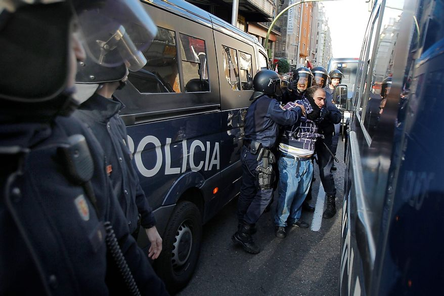 Riot police arrest a protestor during a general strike in Madrid, Spain, Wednesday, Nov. 14, 2012. Spain's main trade unions stage a general strike, coinciding with similar work stoppages in Portugal and Greece, to protest government-imposed austerity measures and labor reforms. The strike is the second in Spain this year. (AP Photo/Andres Kudacki)