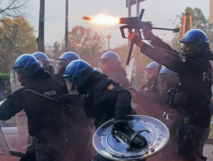 A police officer fires tear gas as police face demonstrators during a protest against Italian Government austerity measures in Turin, Italy, Wednesday, Nov. 14, 2012. Workers across the European Union sought to present a united front against rampant unemployment and government spending cuts Wednesday with a string of strikes and demonstrations across the region. Protesters clashed with police in various demonstrations in Rome, Milan, Turin, Padua and Brescia. (AP Photo/Fabio Ferrari, Lapresse)