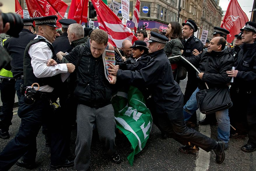 Police officers try to push protesters back onto the pavement Nov. 14, 2012, after they blocked traffic on Oxford Street in London while demonstrating against the dismissal of 28 workers employed by contractors on the Crossrail transport project, whom they say were fired for being trade union members. (Associated Press)