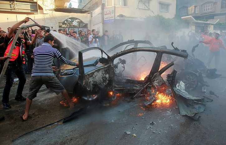 People gather around a wreckage of the car in which was killed Ahmed Jabari, head of the Hamas military wing in Gaza City, Wednesday, Nov. 14, 2012. The Israeli military said its assassination of the Hamas military commander marks the beginning of an operation against Gaza militants. (AP Photo/Adel Hana)