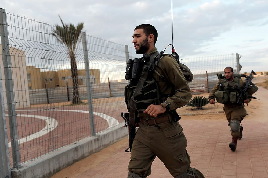 Israelis soldiers run to a rocket shelter as a siren sounds signaling an attack coming from the nearby Gaza Strip in Neva settlement, near the Israel-Egypt border, Wednesday, Nov. 14, 2012. (AP Photo/Tsafrir Abayov)