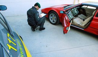 A tax police officer squats Oct. 24, 2012, next to a confiscated Ferrari at the Guardia di Finanza quarters in Pescara, Italy. (Associated Press/Courtesy of the Guardia di Finanza)