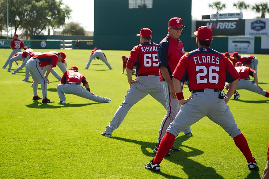 **FILE** Washington Nationals manager Davey Johnson (second from right) talks Feb. 29, 2012, with Washington Nationals catcher Jesus Flores (26) during spring training at Space Coast Stadium in Viera, Fla. (Andrew Harnik/The Washington Times)