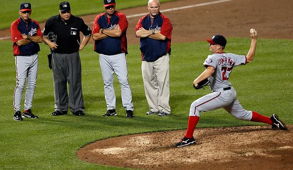 Washington Nationals manager Davey Johnson (far left) looks on June 22, 2012, with team coaches and umpire Brian O'Nora as starting pitcher Jordan Zimmermann throws a pitch after being hit by a ball in the sixth inning of an interleague baseball game against the Baltimore Orioles in Baltimore. (Associated Press)