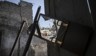 A street of destroyed buildings is reflected Nov. 13, 2012, in a mirror used by rebel fighters to keep an eye on a Syrian army position in Aleppo, Syria. (Associated Press)