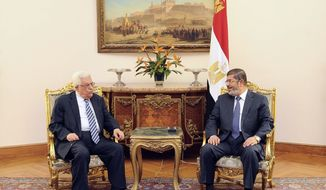 In this photo, released by the Egyptian Presidency, Palestinian President Mahmoud Abbas, left, meets with Egyptian President Mohammed Morsi, right, in Cairo, Egypt, Tuesday, Nov. 13, 2012. (AP Photo/Egyptian Presidency)