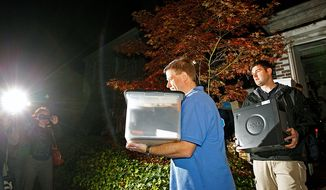 FBI agents carry boxes and a computer from the home of Paula Broadwell, the woman whose affair with retired Gen. David Petraeus led to his resignation as CIA director, in the Dilworth neighborhood of Charlotte, N.C., Tuesday, Nov. 13, 2012. (AP Photo/Chuck Burton)