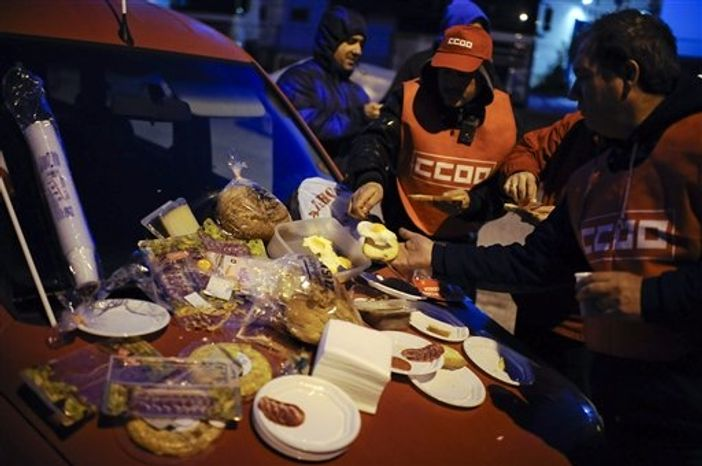 Trade Unions take a breakfast early in the morning outside of a factory during a general strike against government austerity measures, in Pamplona, northern Spain, Wednesday, Nov. 14, 2012. A Spanish Interior Ministry official says 32 people have been arrested and 15 people treated for minor injuries in disturbances as a general strike in Spain against austerity measures and economic reforms began. (AP Photo/Alvaro Barrientos)