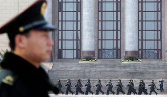 Chinese soldiers march outside the Great Hall of the People in Beijing where the se¿ inner circle of Chinese political power, was paraded in front of assembled media Thursday, the day after 18th Communist Party Congress ended. (Associated Press)