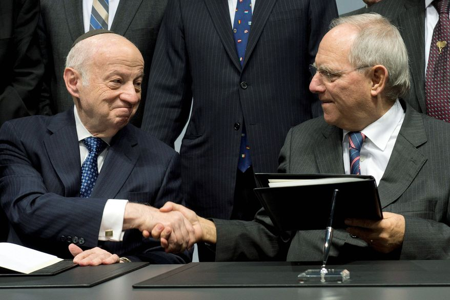 Julius Berman (left), chairman of the Jewish Claims Conference, and German Finance Minister Wolfgang Schaeuble shake hands after signing a new article of the Luxembourg Agreement at a ceremony for the 60th anniversary of the contract in Berlin on Thursday. (Associated Press)