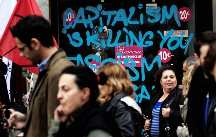 Protesters march past a closed shop during a union demonstration Wednesday in Thessaloniki, Greece. Officials announced Europe has been in the second leg of a double-dip recession since the fourth quarter of last year. The overall European unemployment rate is at a record-high 11.6 percent, and it is hovering around 25 percent in Greece and Spain. (Associated Press)