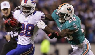 Buffalo Bills running back C.J. Spiller (28) is tackled by Miami Dolphins' Reshad Jones (20) during the first half of an NFL game on Thursday, Nov. 15, 2012, in Orchard Park, N.Y. (AP Photo/Bill Wippert)