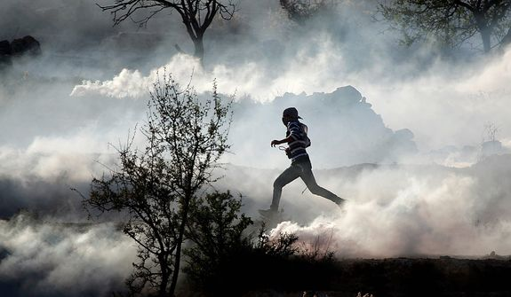 A Palestinian demonstrator runs through a cloud of tear gas during clashes against Israel's operations in Gaza Strip, outside Ofer, an Israeli military prison near the West Bank city of Ramallah, on Nov. 15, 2012. (Associated Press)