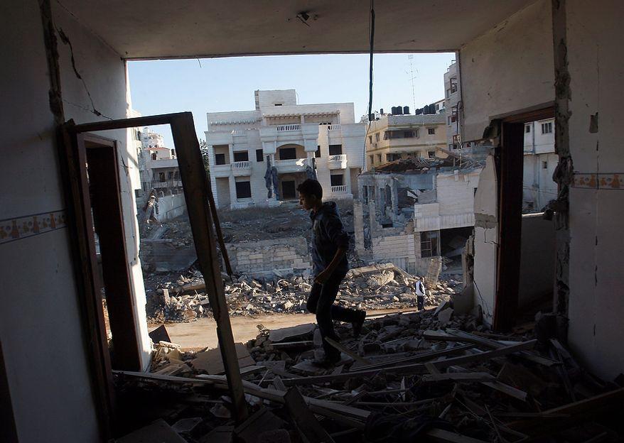 A Palestinian youth walks Nov. 15, 2012, through a damaged apartment in Gaza City hit in an Israeli strike. (Associated Press)