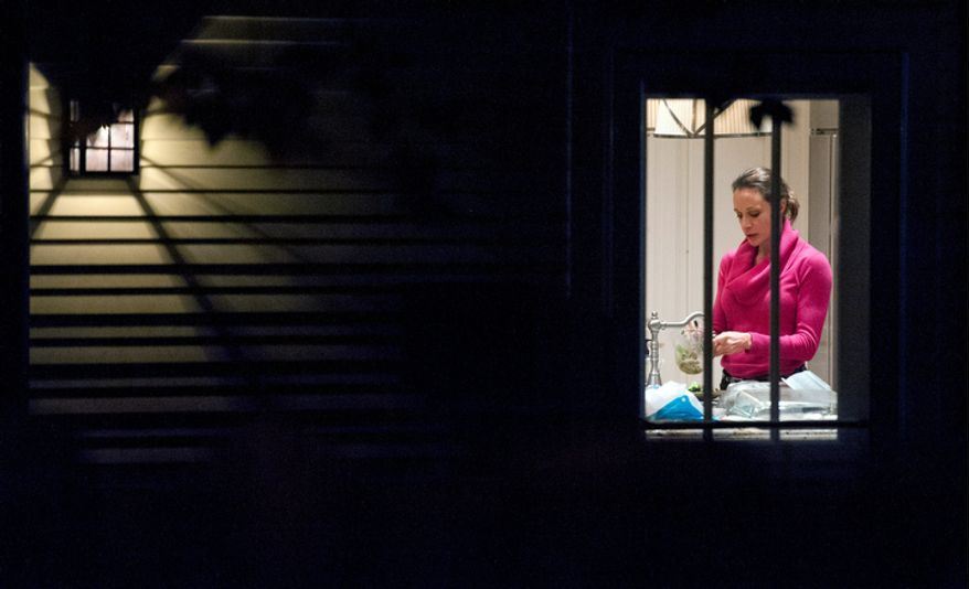 Paula Broadwell is visible through the window in the kitchen of her brother's house in Washington, Tuesday, Nov. 13, 2012. Broadwell is CIA Director David Petraeus' biographer, with whom he had an affair that led to his abrupt resignation last Friday. It was Broadwell's threatening emails to Jill Kelley, a Florida woman who is a Petraeus family friend, that led to the FBI's discovery of communications between Broadwell and Petraeus indicating they were having an affair. (AP Photo/Cliff Owen)