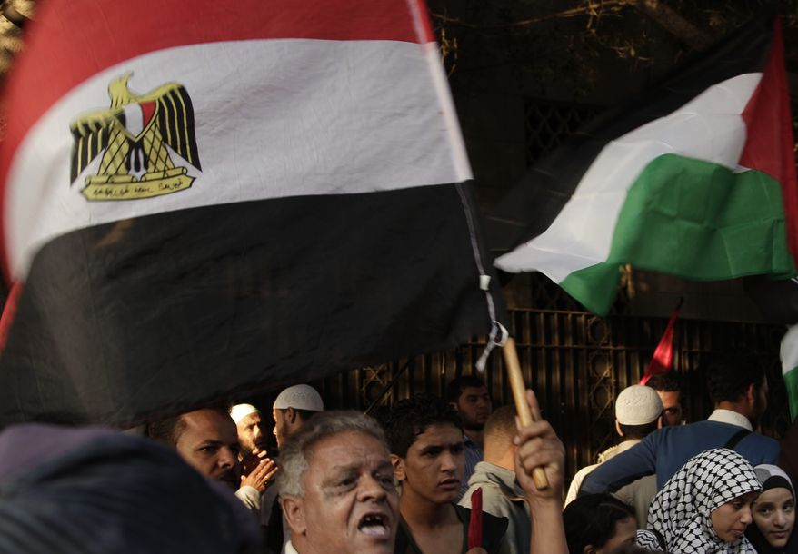 Protesters wave the Egyptian and Palestinian flags Nov. 15, 2012, during a protest in solidarity with Gaza after Israel launched its operation the previous day with the assassination of Hamas' top military commander in front of the Arab League building in Cairo. (Associated Press)