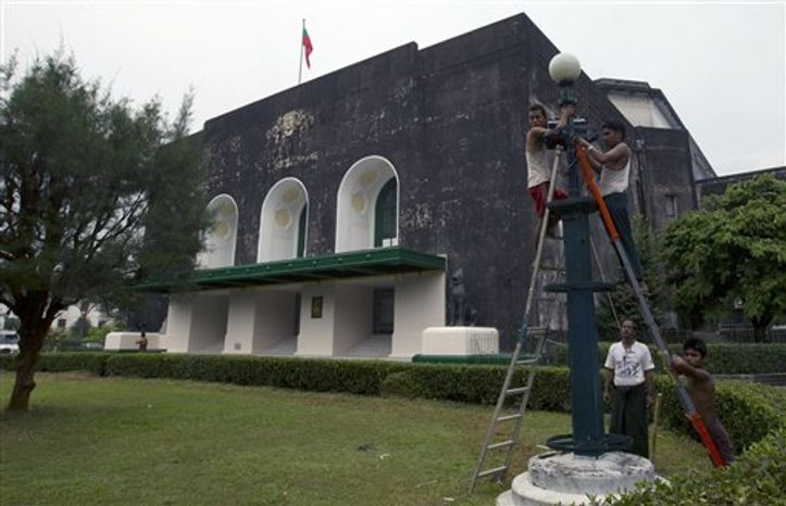 Workers repair light fixtures out side the Yangon University's Convocation Hall, where U.S. President Obama is anticipated to deliver a lecture on his historic visit in Yangon, Myanmar, Thursday, Nov. 15, 2012. Obama, who visits Myanmar on November 19, will meet democracy icon Aung San Suu Kyi and President Thein Sein on the first visit to the country by a sitting US president. (AP Photo/Gemunu Amarasinghe)