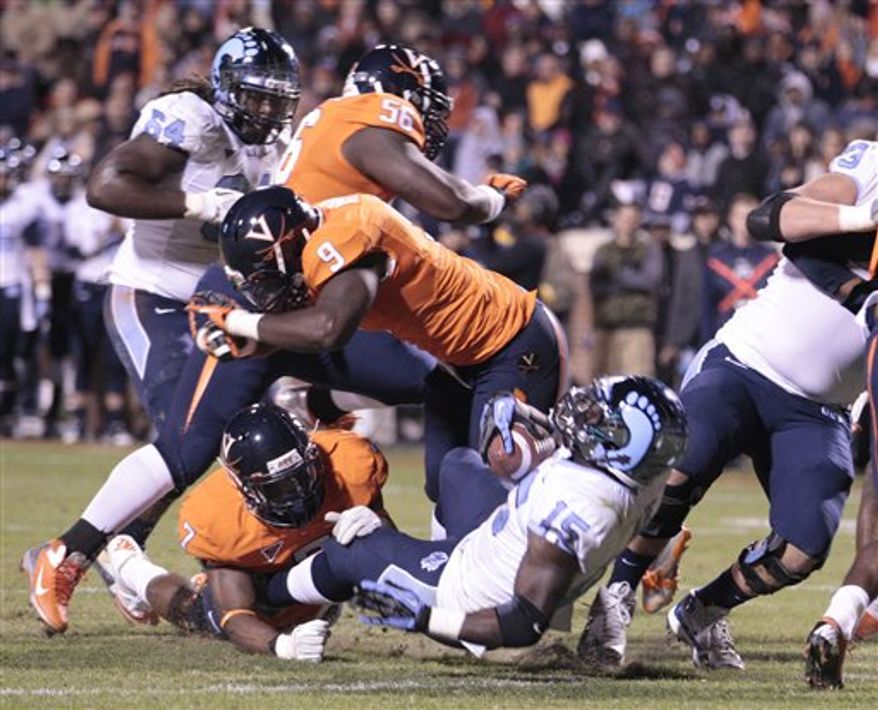 North Carolina running back A.J. Blue (15) backs in for a touchdown as Virginia defensive end Eli Harold (7) and linebacker LaRoy Reynolds (9) try to make the stop during the first half of an NCAA football game at Scott stadium Thursday, Nov. 15, 2012 in Charlottesville, VA (AP Photo/Steve Helber)