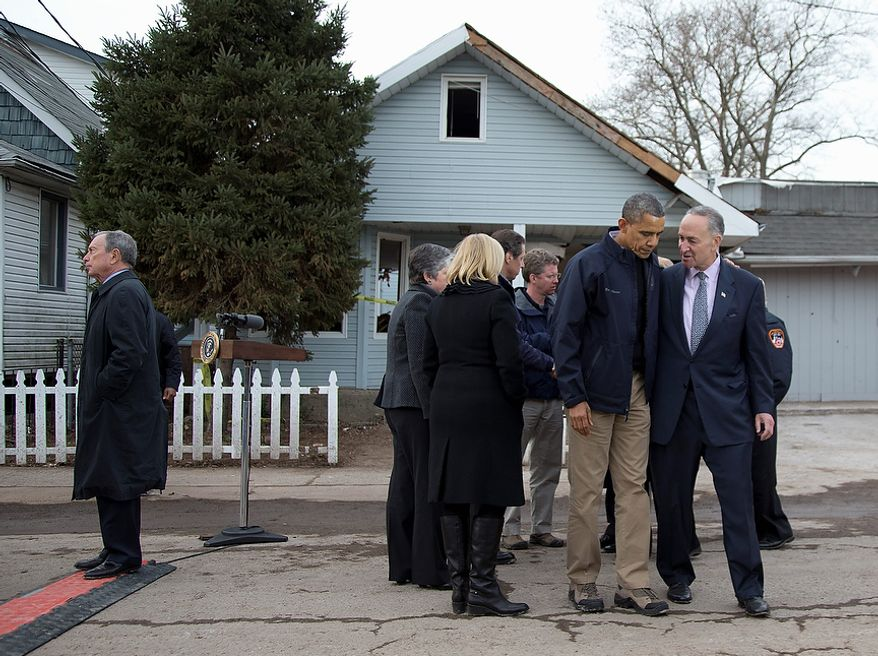 President Barack Obama walks with Sen. Charles Schumer, D-N.Y., from a new conference on Cedar Grove Avenue, a street significantly impacted by Superstorm Sandy, on the Staten Island borough of New York, Thursday, Nov. 15, 2012. At left is New York City Mayor Michael Bloomberg. (AP Photo/Carolyn Kaster)