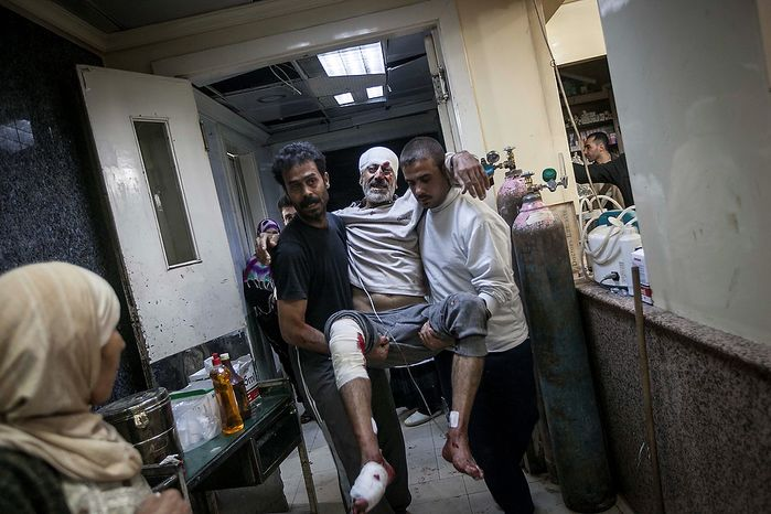 In this Tuesday, Nov. 13, 2012 photo, a Syrian man is carried in the arms of his relatives at a hospital after he was injured by a mortar shell explosion in the Bab Al-Nayrab neighborhood of Aleppo, Syria. (AP Photo/Narciso Contreras)