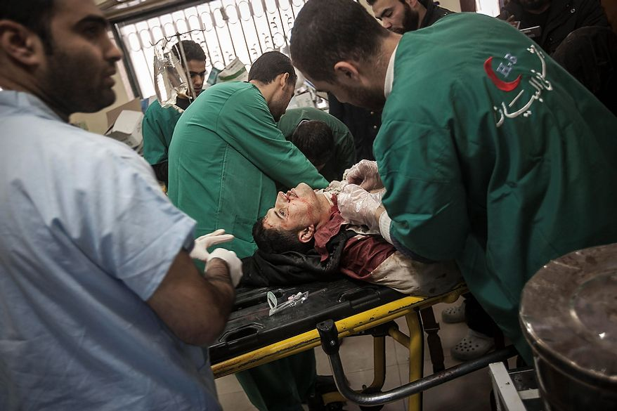 In this Wednesday, Nov. 14, 2012 photo, a Syrian resident gets emergency medical attention as he arrives to a hospital after he was injured by a mortar attack in Aleppo, Syria. (AP Photo/Narciso Contreras)