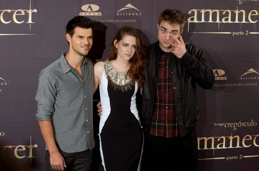 """American actor Taylor Lautner, left American actress Kristen Stewart, center and British actor Robert Pattinson pose during a photo call for the film """"The Twilight Saga: Breaking Dawn Part 2""""  in Madrid, Spain, Thursday, Nov. 15, 2012. ( AP Photo/Gabriel Pecot)"""
