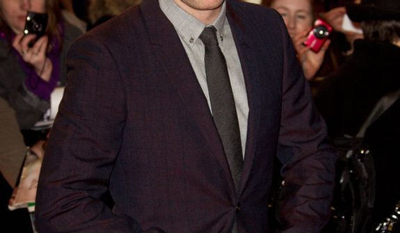 Robert Pattinson, who plays Edward Cullen, adjusts his suit as he arrives for the European Premiere of The Twilight Saga: Breaking Dawn Part 2, the final film in the series, in Leicester Square, central London, Wednesday, Nov. 14, 2012. (Photo by Joel Ryan/Invision/AP)