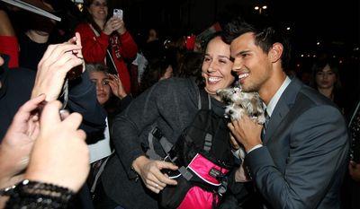 "Taylor Lautner, right, poses for fans at the world premiere of ""The Twilight Saga: Breaking Dawn Part 2"" at the Nokia Theatre on Monday, Nov. 12, 2012, in Los Angeles. (Photo by Matt Sayles/Invision/AP)"