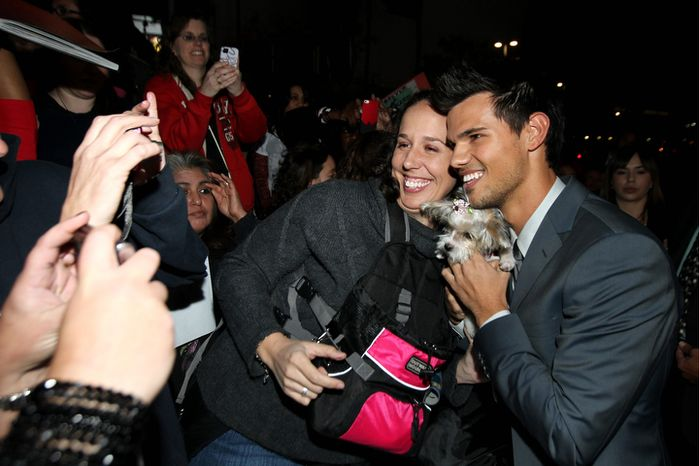 """Taylor Lautner, right, poses for fans at the world premiere of """"The Twilight Saga: Breaking Dawn Part 2"""" at the Nokia Theatre on Monday, Nov. 12, 2012, in Los Angeles. (Photo by Matt Sayles/Invision/AP)"""