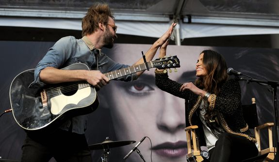"Nikki Reed, right, a cast member in the film ""The Twilight Saga: Breaking Dawn Part 2,"" gets a high five from her husband, singer Paul McDonald, after they performed together onstage during the Twilight Fan Camp Concert outside Nokia Theater L.A. Live, Saturday, Nov. 10. 2012, in Los Angeles. The world premiere of the film will be held at Nokia Theater L.A. Live on Monday. (Photo by Chris Pizzello/Invision/AP)"