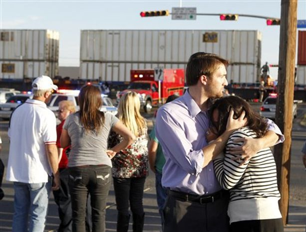 "Bystanders react as emergency personnel work the scene where a trailer carrying wounded veterans in a parade was struck by a train in Midland, Texas, Thursday, Nov. 15, 2012. ""Show of Support"" president and founder Terry Johnson says there are ""multiple injuries"" after a Union Pacific train slammed into the trailer, killing at least four people and injuring 17 others. (AP Photo/Reporter-Telegram, James Durbin)"