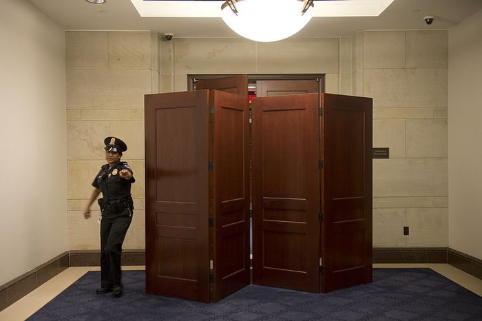 A U.S. Capitol Police officer comes out of the room where Gen. David Petraeus is set to testify before the Senate Intelligence Committee about the Benghazi attack at the U.S. Capitol on Friday, Nov. 16, 2012. The general was expected to say that he knew the attack was terror-based from the beginning. Security was tight in the Capitol complex, and the media were not allowed in the hearing rooms. (Barbara L. Salisbury/The Washington Times)