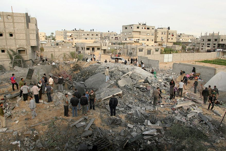 Palestinians inspect the rubble of the destroyed house of Hamas militant Mohammad Abu Shmala, following an Israeli air strike in Rafah, southern Gaza Strip, Friday, Nov. 16, 2012. (AP Photo/Eyad Baba)